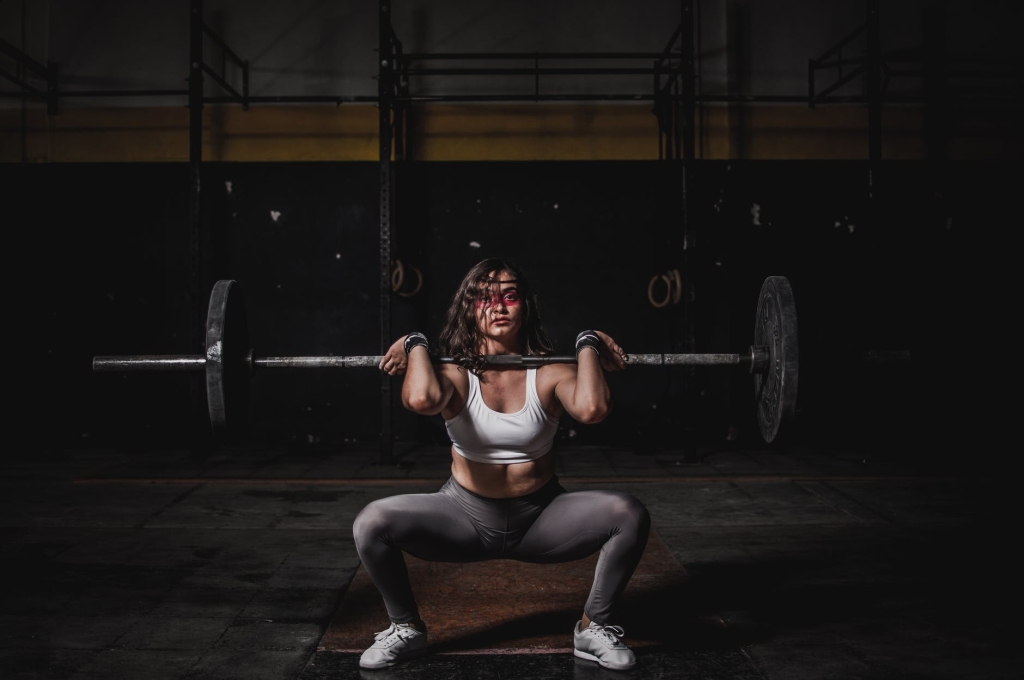 Young woman performing a front squat at the gym